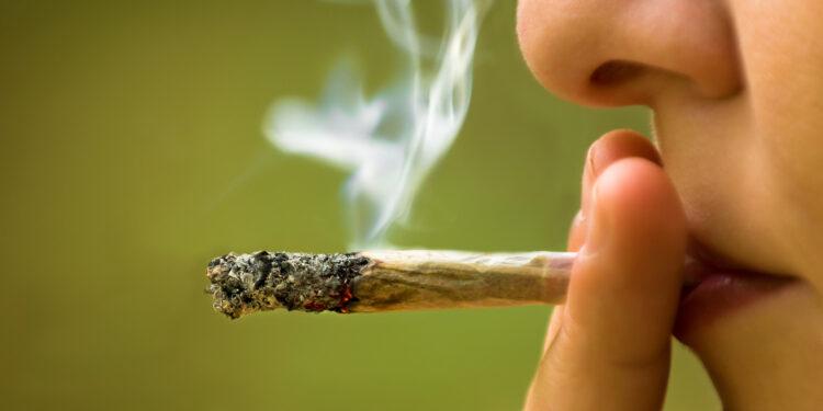 Junge Frau zieht an einem Joint