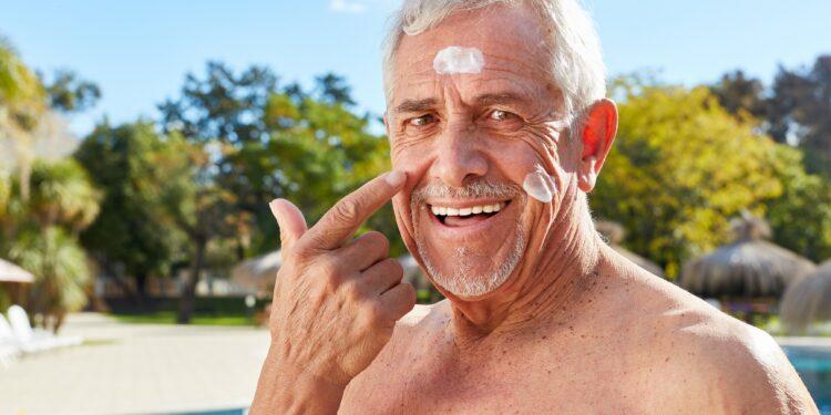 Älterer Mann cremt sein Gesicht mit Sonnenschutzmittel ein