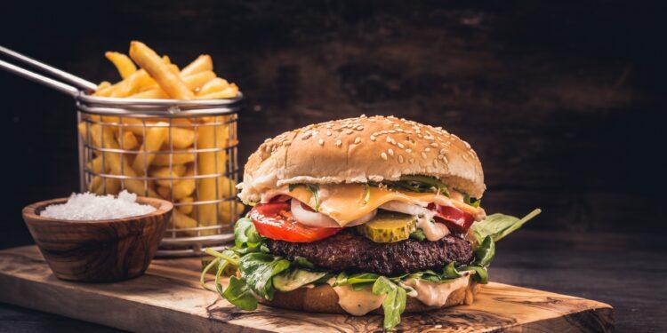 Ein Burger mit Pommes auf einem Holzbrett