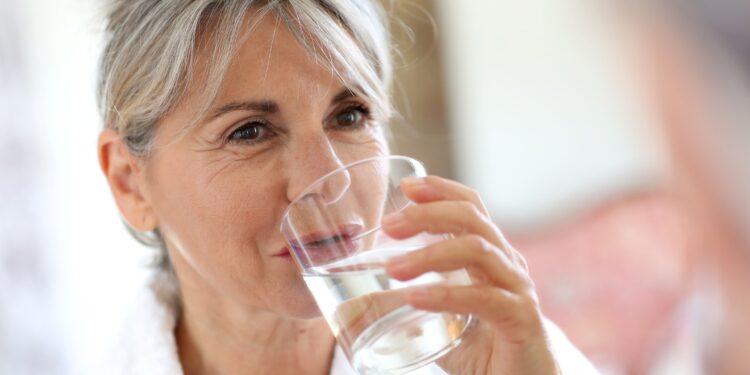 Eien Seniorin im Morgenmantel trinkt ein Glas Wasser