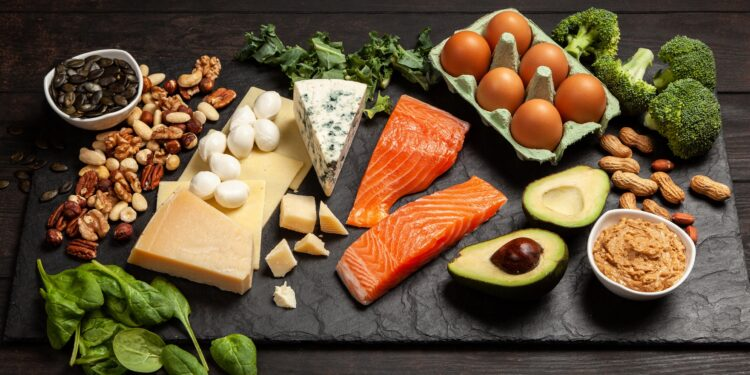 Verschiedene proteinreiche Lebensmittel wie Fisch und Käse auf einer dunklen Platte
