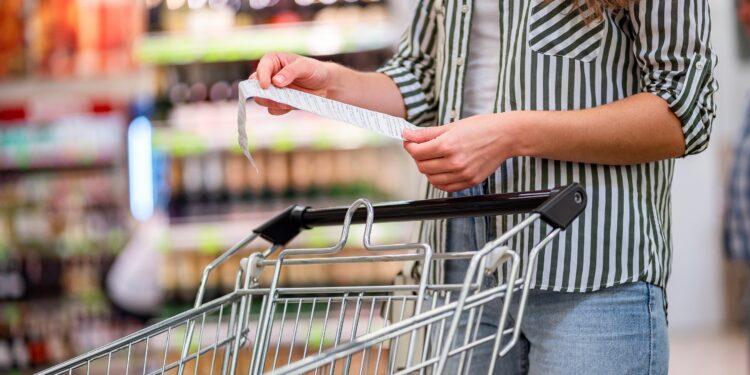 Frau mit Einkaufwagen kontrolliert den Kassenbon