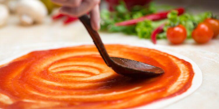 Auf einem Pizzateig wird Tomatensauce verteilt