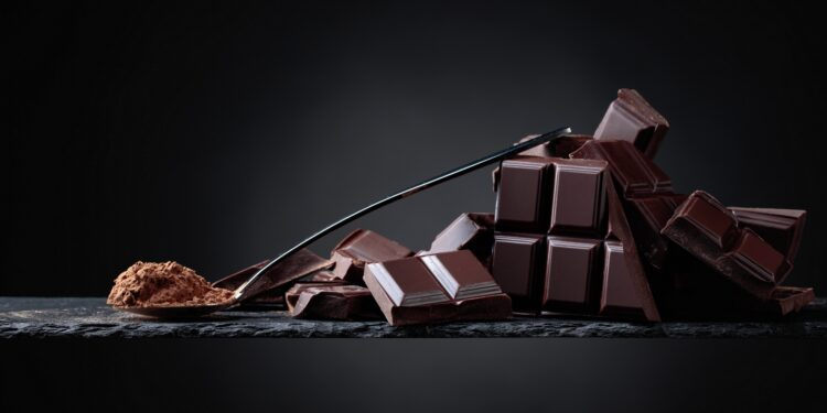 Schokoladenstücke und Schokoladenpulver in einem kleinen Löffel vor dunklem Hintergrund