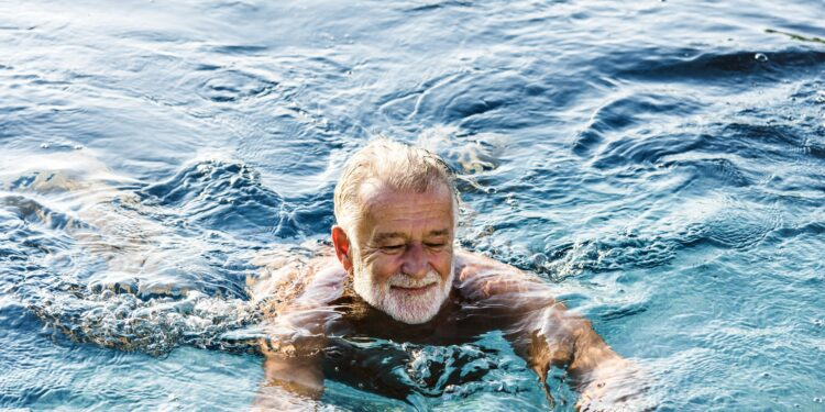 Älterer Mann schwimmt im Swimmingpool