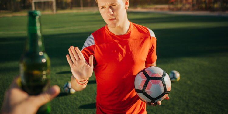 Ein Fußballer mit eine Fußball in der Hand weist eine angebotene Flasche Bier zurück