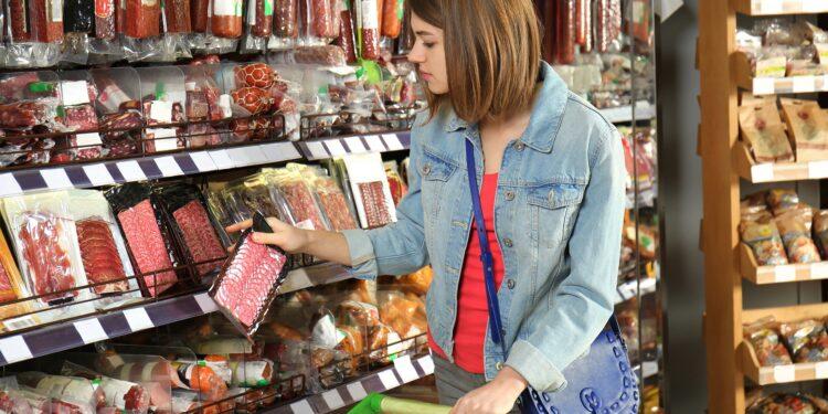 Eine Frau nicht sich eine Packung Salami aus einem Regal im Supermarkt.
