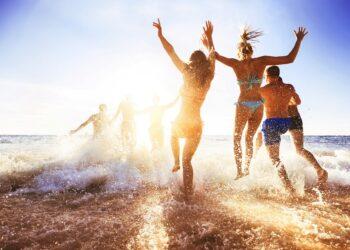 Mehrere junge Menschen laufen bei Sonnenuntergang ins Meer