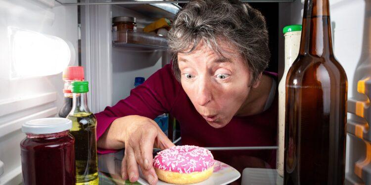Eine Frau greift nach einem Donat im Kühlschrank.