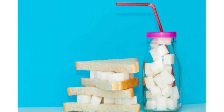 Ein Toast ist mit Zuckerwürfel belegt, daneben steht ein Glas, das mit Zuckerwürfeln befüllt ist.