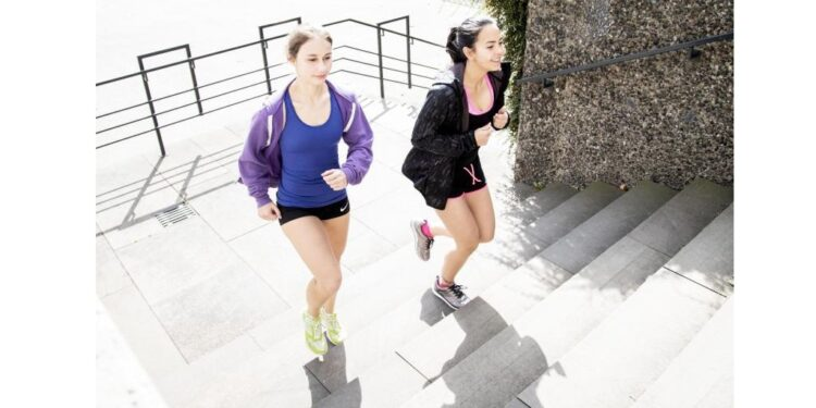 Zwei Frauen joggen eine Treppe hinauf.