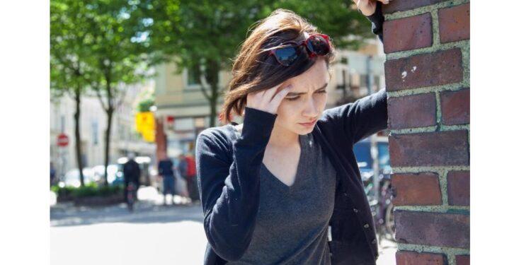 Eine Frau stützt sich an einer Wand ab und hält eine Hand an die Schläfe.