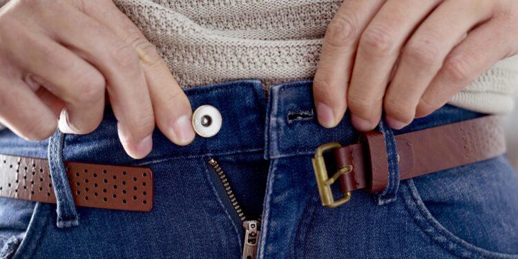 Junger Mann versucht den Knopf seiner Hose zu schließen
