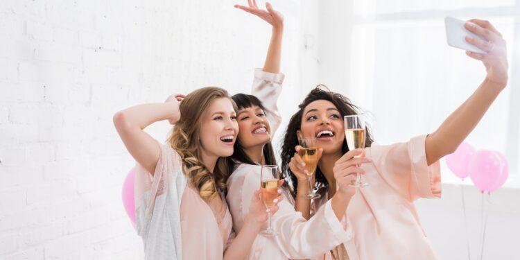 Drei Frauchen trinken Sekt und fotografieren sich mit einem Smartphone.