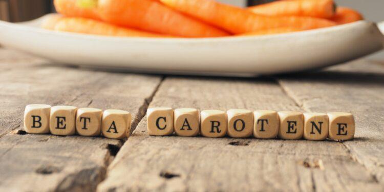 Holzwürfel mit dem englischen Wort für Beta-Carotin vor einem Teller mit Karotten auf einem Holztisch