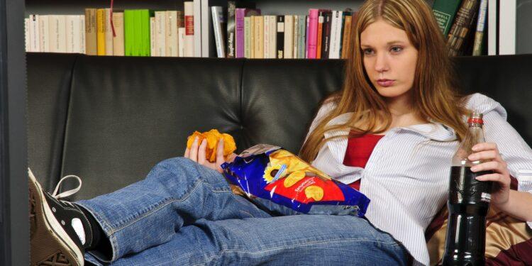 Eine junge Frau sitzt auf dem Sofa, trinkt Cola und isst Pommes.