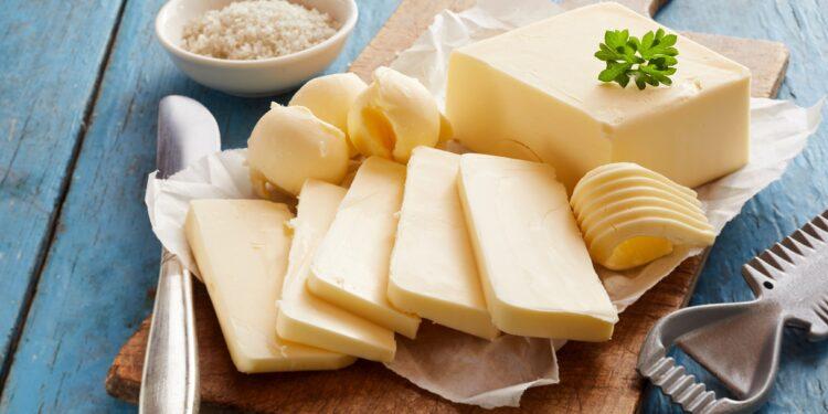 Eine Stück Butter liegt auf einem Holzbrettchen.