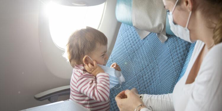 Frau mit Mund-Nasen-Schutz sitzt neben ihrem Kind im Flugzeug