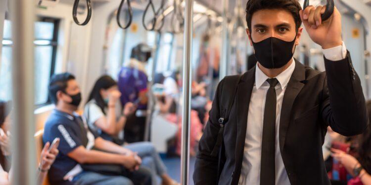 Junger Mann mit Anzug trägt in der U-Bahn eine Mund-Nasen-Bedeckung