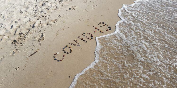 Strand auf dem der Schriftzug COVID-19 mit Steinen gelegt wurde