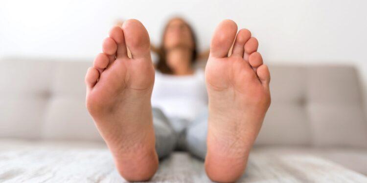 Junge Frau sitzt auf dem Sofa und streckt die Beine aus