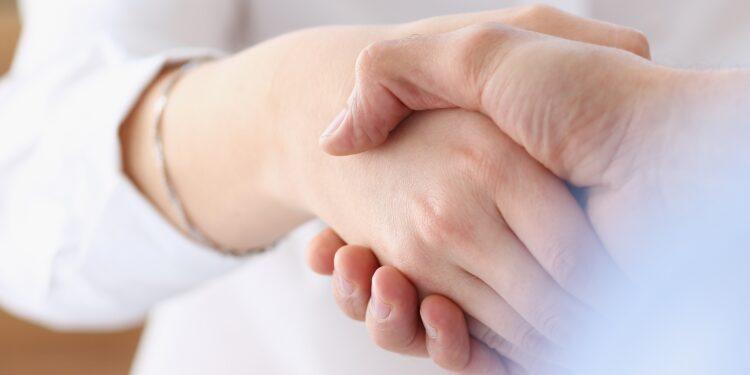 Zwei Personen reichen sich die Hände.
