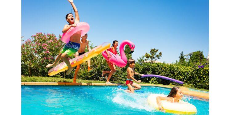 Fünf Kinder springen in einen Swimmingpool.
