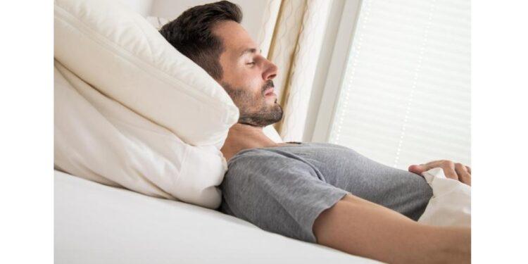Ein Mann liegt in Rückenlage auf einer Matratze.