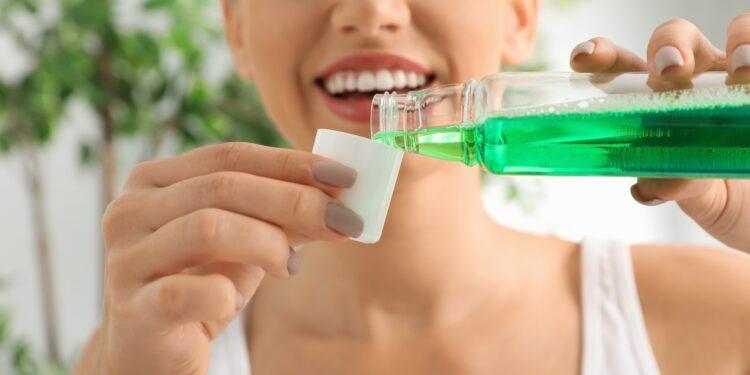 Frau gießt Mundspülung in einen kleinen Becher.