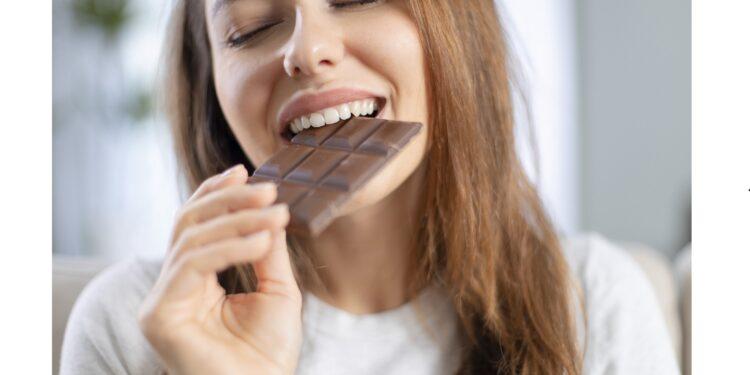 Eine Frau beißt genussvoll in eine Tafel Schokolade.