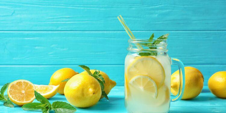 Ein Glas mit Zitronenwasser und einem Strohhalm und mehrere frische Zitronen auf einem Holztisch