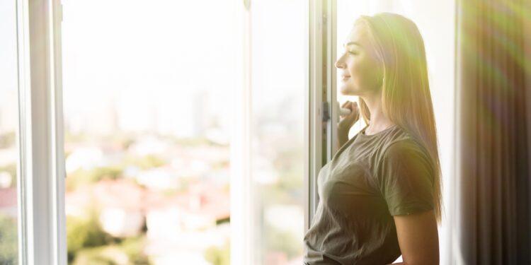 Eine Frau öffnet ein Fenster.