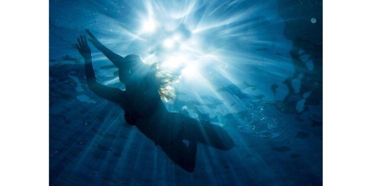 Ein Frau schwimmt bei strahlendem Sonnenschein im Wasser.