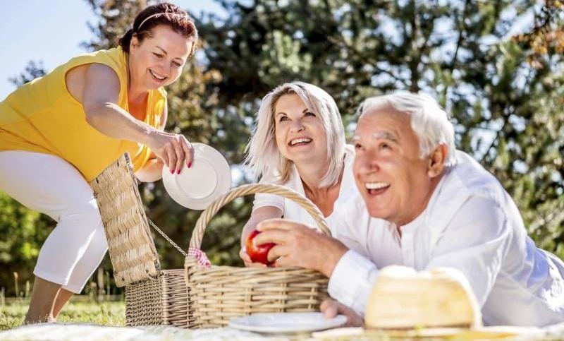 Drei ältere Personen machen ein Picknick auf einer Wiese.