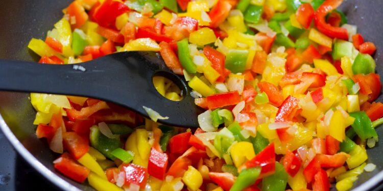 Eine Pfanne voller Gemüse und ein Kochlöffel