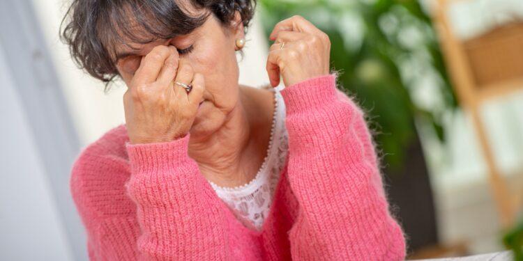 Erschöpfte Seniorin reibt sich die Nasenwurzel