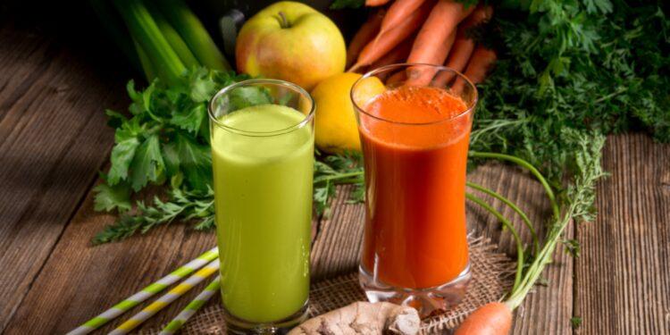 Frisch gepresste Säfte und frisches Obst und Gemüse auf einem Holztisch