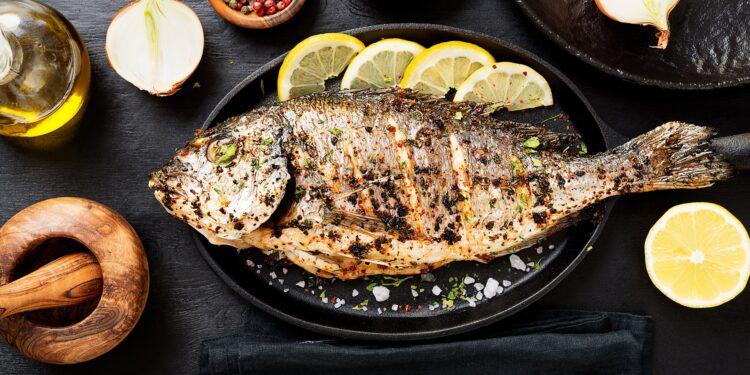 Gegrillter Fisch auf einem Teller mit Zitronenscheiben