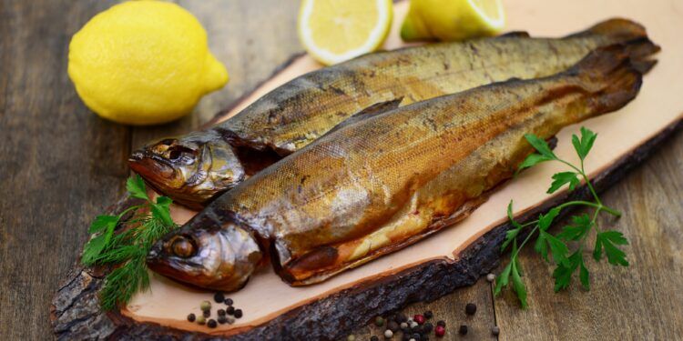 Zwei geräucherte Fische auf einem Holzbrett mit Zitronen und Petersilie