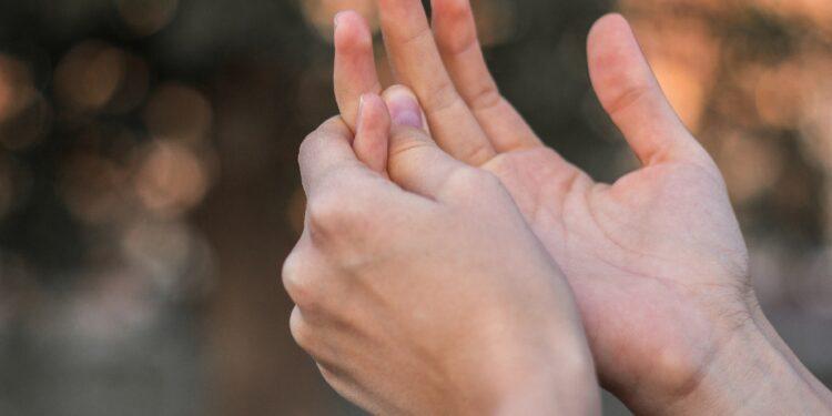 Junge Frau hält ihre schmerzende Hand