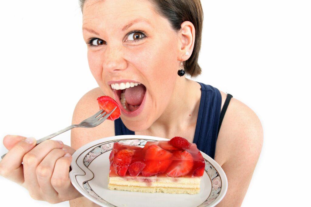 Frau mit weit geöffnetem Mund hält einen Teller mit einem Stück Erdbeerkuchen