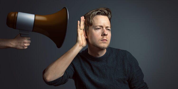 Ein Mann hält sein Ohr an ein Megafon.