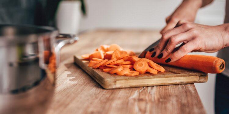 Frau schneidet Karotten in dünne Scheiben
