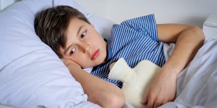 Ein Junge liegt mit einer Wärmflasche auf dem Bauch im Bett.