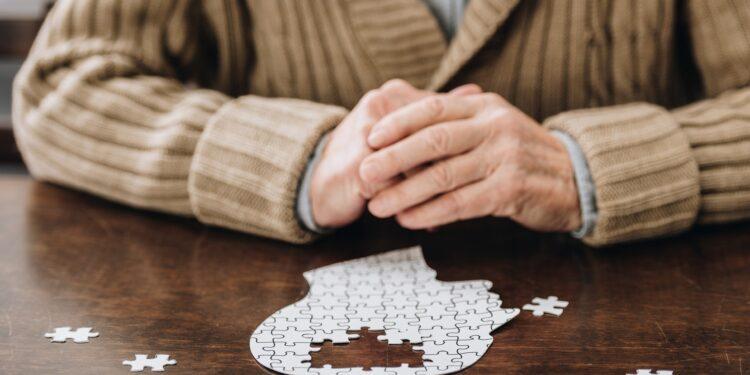 Person löst Puzzle in Form eines Kopfes.