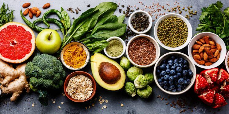 Gesunde Lebensmittel wie Gemüse, Obst und Hülsenfrüchte auf einem Tisch