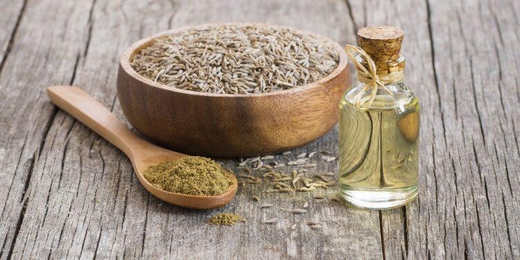 Kreuzkümmel-Samen und Öl auf einer Holzoberfläche.