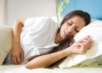 Eine Frau liegt im Bett und hält sich eine Hand auf den Bauch.