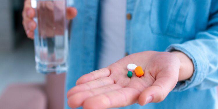 Mann hält in der linken Handfläche drei Tabletten, in der rechten Hand ein Glas Wasser