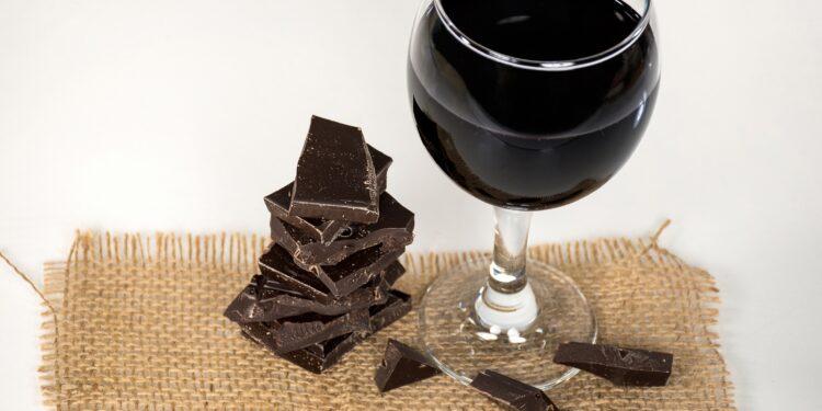 Ein Glas Rotwein und dunkle Schokolade auf einem Stück Stoff